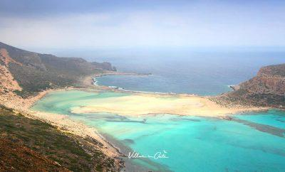 Why do the beaches at Elafonisi and Balos have pink sand?